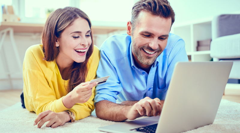 Happy couple doing online shopping with credit card and laptop