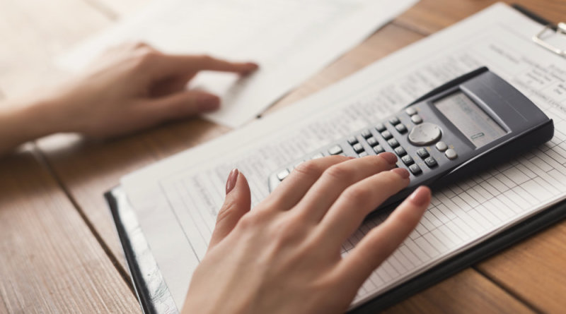 Closeup of woman hands counting on calculator
